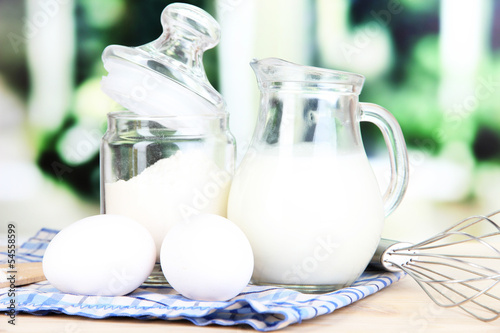 Ingredients for dough on wooden table on window background