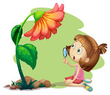 A girl holding a magnifying glass under a flower