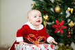 kid girl dressed as Santa Claus in front of Christmas tree with