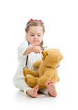 Adorable girl with clothes of doctor playing with toy over white