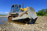 Bulldozer at work to strengthen the shoreline of the river poster