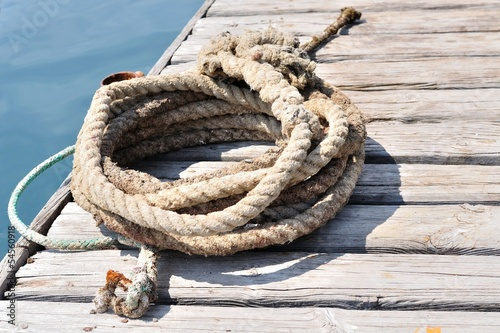 Coiled marine rope on wooden pier. Podgora, Croatia
