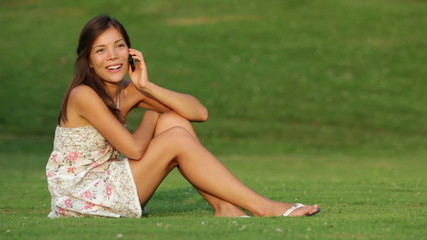 Woman talking on smart phone outdoors on grass