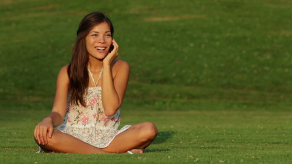Girl talking on mobile phone outdoors laughing