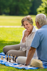 Elderly couple playing chess in the park