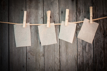 paper attach to rope with clothes pins on wooden background