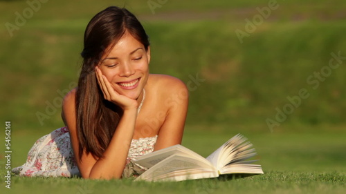 Girl reading book in park smiling happy