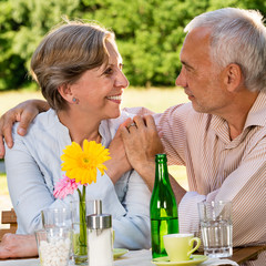 Retired couple sitting at table holding hands