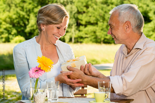 Retired Caucasian couple holding gift