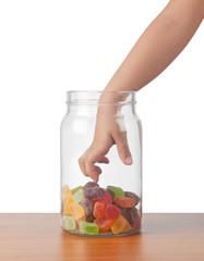 Child's hand reaching out to take candy from a jar