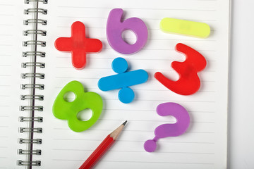 Symbols of numbers and mathematical signs on a notepad