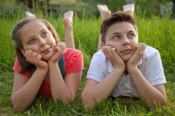 Mädchen und Junge träumen auf einer Wiese