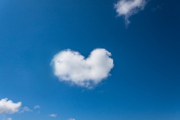 Heart shaped cloud in the blue sky background.