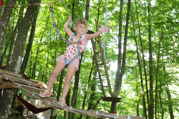young happy child girl in adventure park in safety equipment