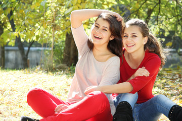 two young happy girls in autumn park outdoor portrait