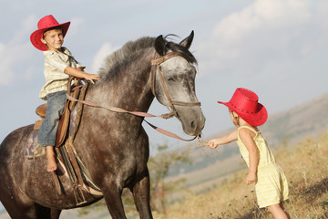 boy and girl riding a horse on farm outdoor portrait
