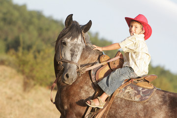 young boy riding a horse outdoors