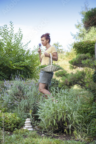 Cute female gardener surrounded with fresh organic herbs
