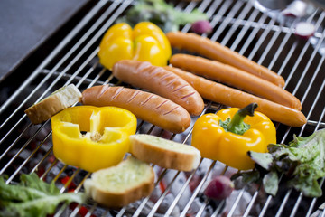 sausage and hot dogs grilling outdoors on a gas barbecue grill