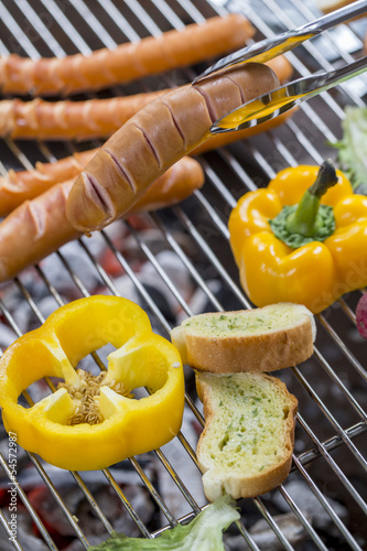 sausage and hot dogs grilling outdoors on a gas barbecue grill.