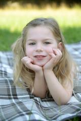 Lächelndes Mädchen liegt auf Decke