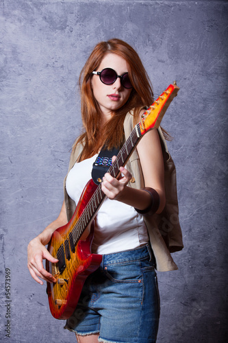 Redhead girl with guitar near wall