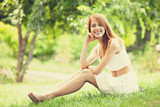 Redhead women lying at green grass