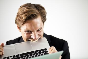Man biting a laptop in frustration