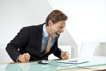 Frustrated businessman shouting at laptop