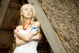 rural woman sitting near by old traditional Ukrainian barn