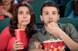 Exciting movie. Shocked young couple eating popcorn and drinking