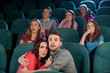 Horror movie. Terrified young couple hugging while watching movi
