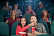 Great movie! Young couple feeding each other while watching movi