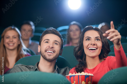 Happy couple at the cinema. Cheerful young couple watching movie