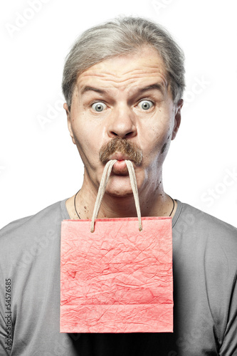 surprised mature man with shopping bag in mouth isolated on whit