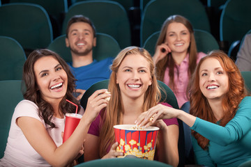Friends at the cinema. Happy young people watching movie at the