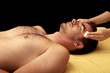 Young man getting facial at spa
