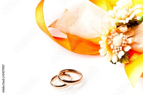 gold wedding rings near ribbon and flowers with space for text