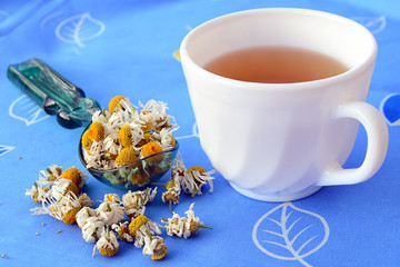 Cup of chamomile tea and dried flowers