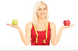 Smiling female holding two apples and measuring tape around her