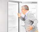 Shocked mature man looking in empty fridge and finding out there
