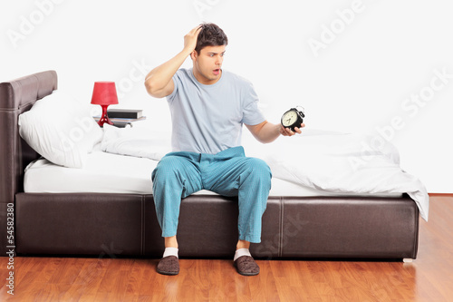 Young upset male sitting on a bed, holding a clock and gesturing