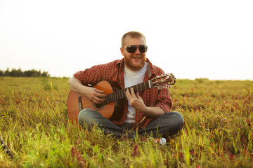 Man in jeans sits and plays guitar