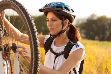 Woman repairing mountain bike.