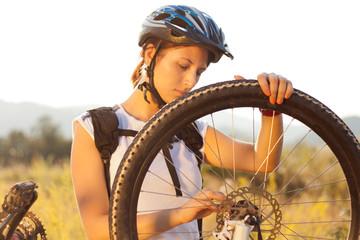 Woman repairing mountain bike.