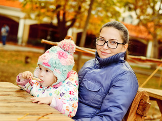 mother with baby daughter in autumn park
