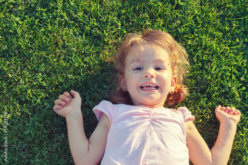Little girl resting in fresh spring grass