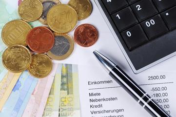 Euroscheine und Münzen mit Kugelschreiber