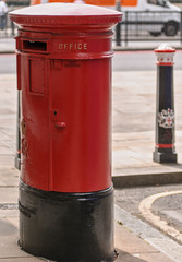Red and black post box with pole