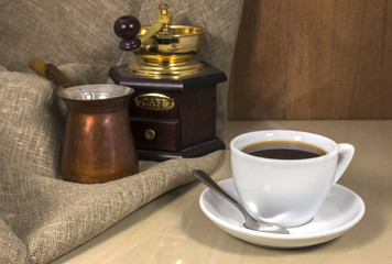 Coffee in a cup on a marble table, hand-mill and Cezve